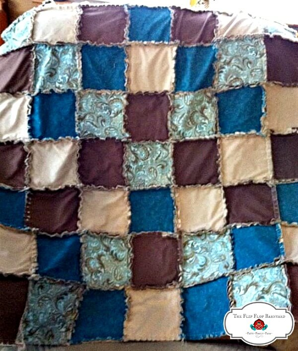 a rag quilt throw with a teal, tan, and brown theme