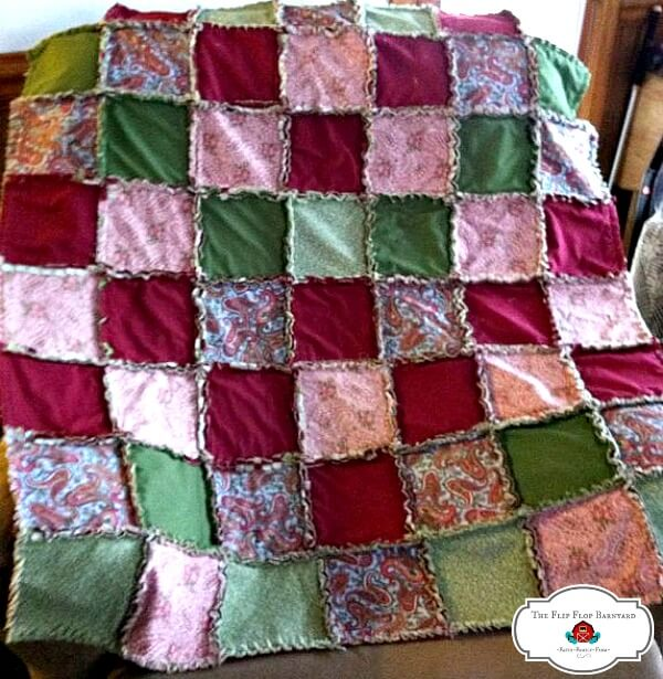 a rag quilt throw with a burgundy, green, and pink theme