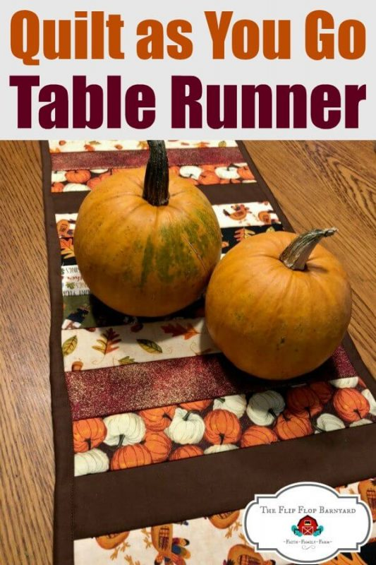 A picture of a fall themed table runner with pumpkins sitting on it as decoration