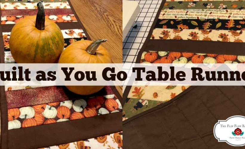 """A photo of a fall themed table runner with pumpkins sitting on it and the words """"Quilt as you go table runner"""" above."""